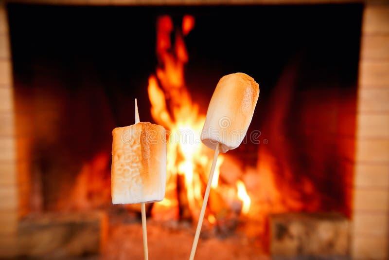 Dois marshmallows nas varas que estão sendo roasted pelo fogo fotografia de stock royalty free