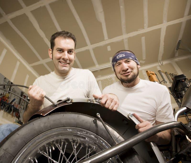 Dois mecânicos da motocicleta que coloc um pára-choque imagens de stock royalty free