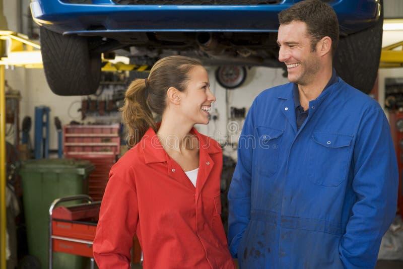 Dois mecânicos que estão no sorriso da garagem fotos de stock