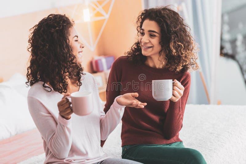 Dois melhores amigos que bisbilhotam ao ter o tempo do chá foto de stock
