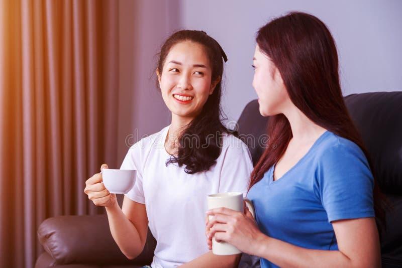 Dois melhores amigos que falam e que bebem uma xícara de café no sofá em foto de stock
