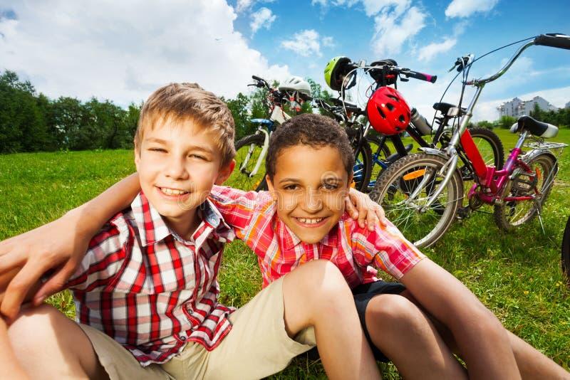 Dois melhores amigos sentam-se na grama e no abraço com braços imagens de stock
