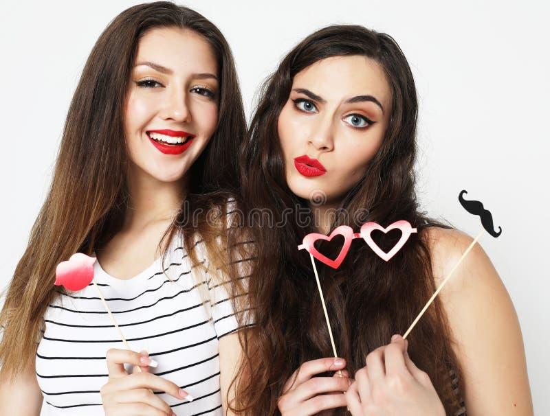 Dois melhores amigos 'sexy' à moda das meninas que guardam as varas de papel do partido fotografia de stock