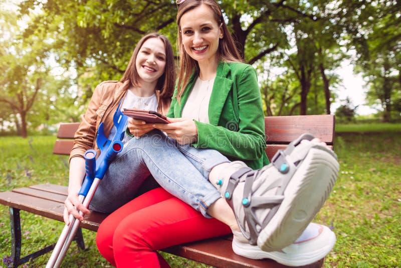 Dois melhores amigos, um com um pé ferido, lendo um livro foto de stock