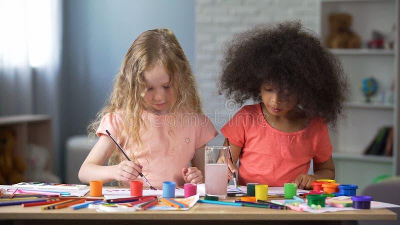 Dois melhores diabos que pintam no jardim de infância, educação pré-escolar, faculdade criadora imagem de stock