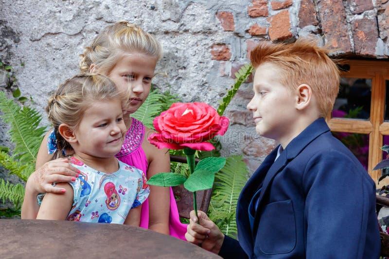 Dois meninas e jogos do menino fotografia de stock
