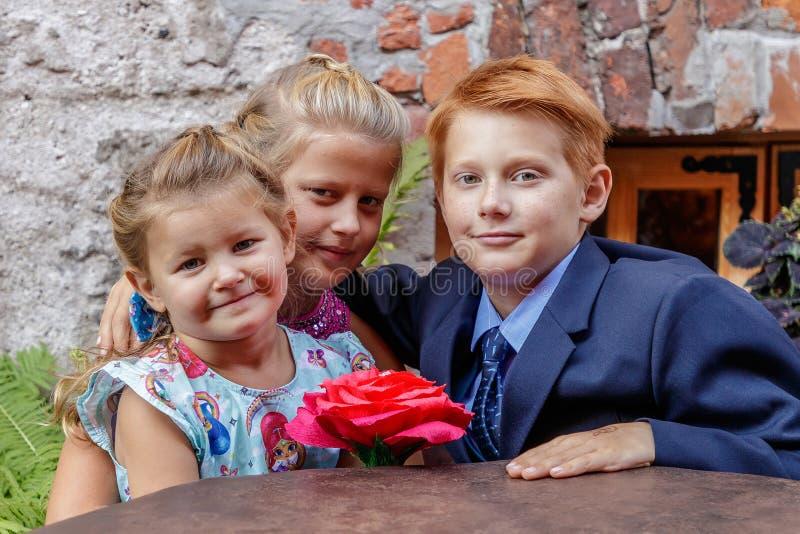 Dois meninas e jogos do menino fotos de stock