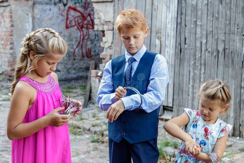 Dois meninas e jogos do menino foto de stock