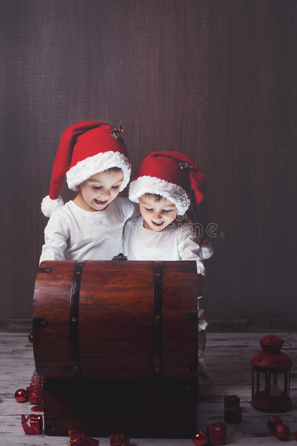 Dois meninos adoráveis, caixa de madeira de abertura, luz de incandescência fotografia de stock
