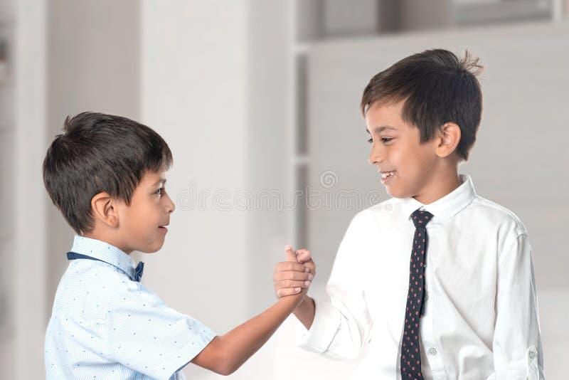 Dois meninos alegres que vestem camisas e laços agitam-se as mãos como prova da amizade fotografia de stock