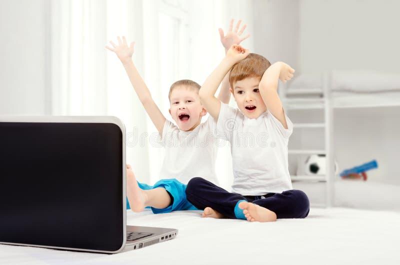 Dois meninos alegres, sentando-se na frente de uma tela do portátil imagens de stock