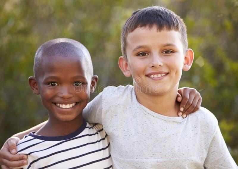 Dois meninos, braços em torno de se que sorri à câmera fora fotos de stock