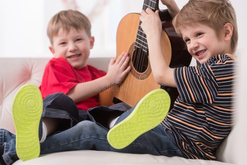 Dois meninos caucasianos que jogam com guitarra acústica imagem de stock
