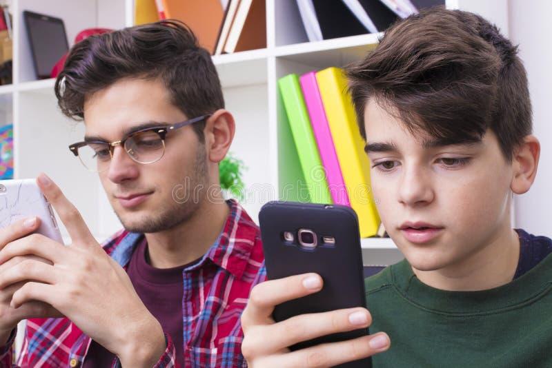 Dois meninos com smartphones fotografia de stock