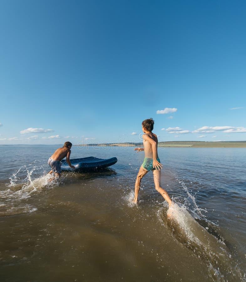 Dois meninos correm na água em um colchão de ar inflável fotos de stock