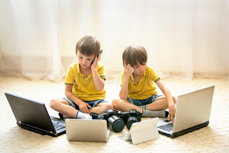 Dois meninos, crianças prées-escolar, tendo o divertimento que joga em casa com co fotos de stock royalty free