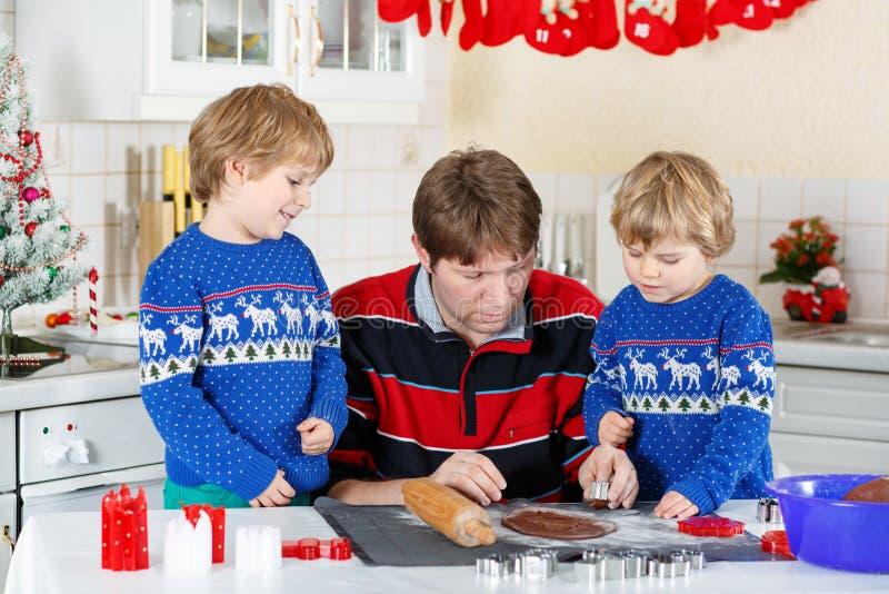 Dois meninos da criança e cookies do pão-de-espécie do cozimento do paizinho imagem de stock