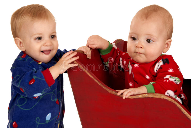 Dois meninos da criança em pijamas do inverno em um trenó imagens de stock royalty free