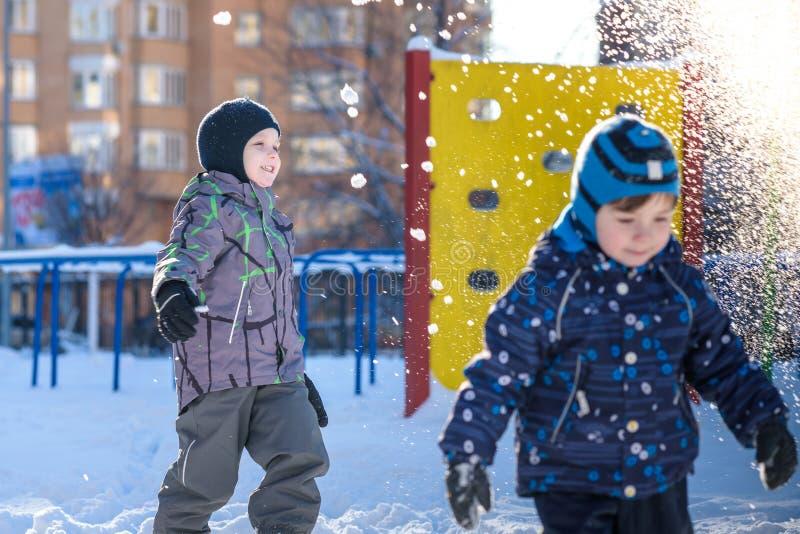 Dois meninos da criança na roupa colorida que joga fora durante a queda de neve Lazer ativo com as crianças no inverno em dias fr foto de stock