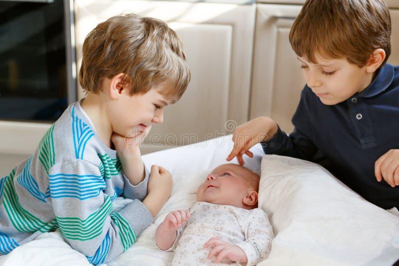 Dois meninos das crianças que jogam com a menina recém-nascida da irmã do bebê imagens de stock