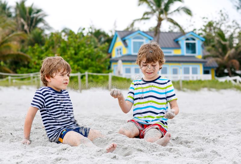 Dois meninos das crianças que têm o divertimento com o castelo da areia da construção na praia tropical, jogo feliz dos melhores  fotografia de stock