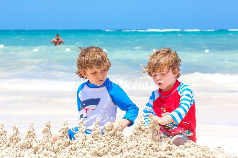 Dois meninos das crianças que têm o divertimento com construção de um castelo da areia na praia tropical na ilha Jogo saudável da fotografia de stock