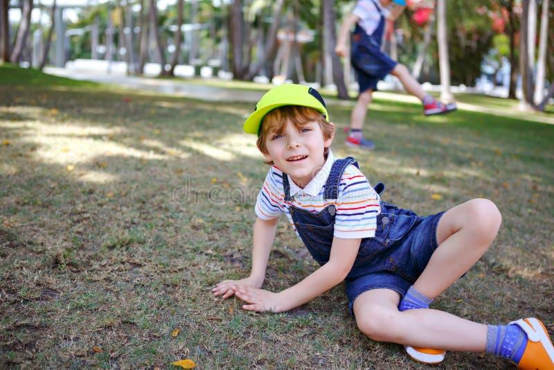 Dois meninos das crianças que têm o divertimento em um parque, melhores amigos felizes que jogam, conceito da amizade Irmãos dos  fotos de stock