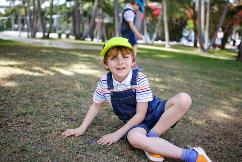 Dois meninos das crianças que têm o divertimento em um parque, melhores amigos felizes que jogam, conceito da amizade Irmãos dos  imagens de stock