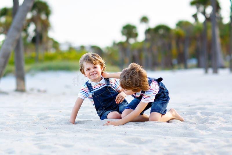 Dois meninos das crianças que têm o divertimento na praia tropical, melhores amigos felizes que jogam, conceito da amizade Irmãos imagens de stock
