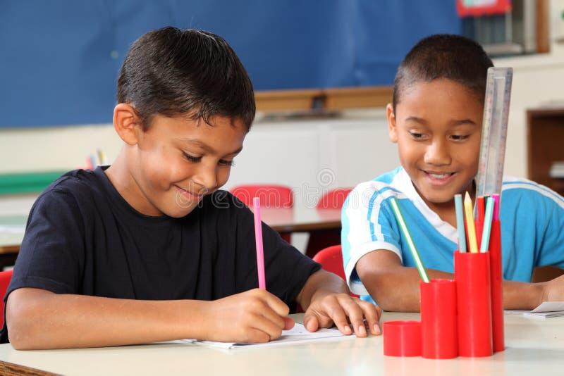 Dois meninos de escola que apreciam sua aprendizagem na classe fotos de stock