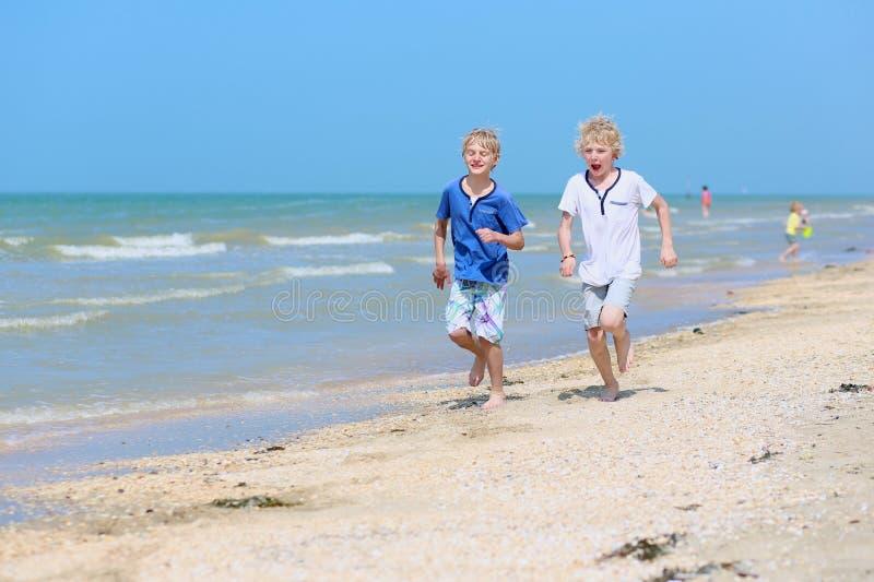 Dois meninos de escola que correm na praia foto de stock