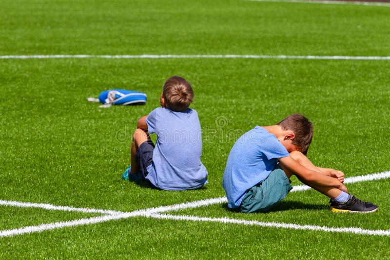 Dois meninos desapontados tristes que sentam-se de volta à parte traseira na grama no estádio imagens de stock royalty free