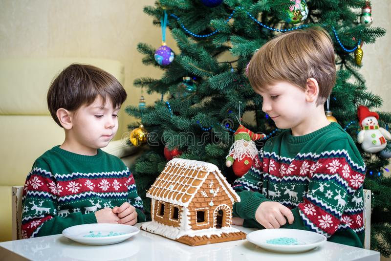 Dois meninos doces, irmãos, fazendo a casa das cookies do pão-de-espécie, decorando em casa na frente da árvore de Natal, do jogo fotografia de stock royalty free