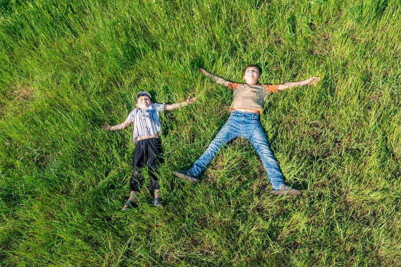 Dois meninos estão encontrando-se na grama, opinião superior amigos felizes e alegres fotografia de stock royalty free