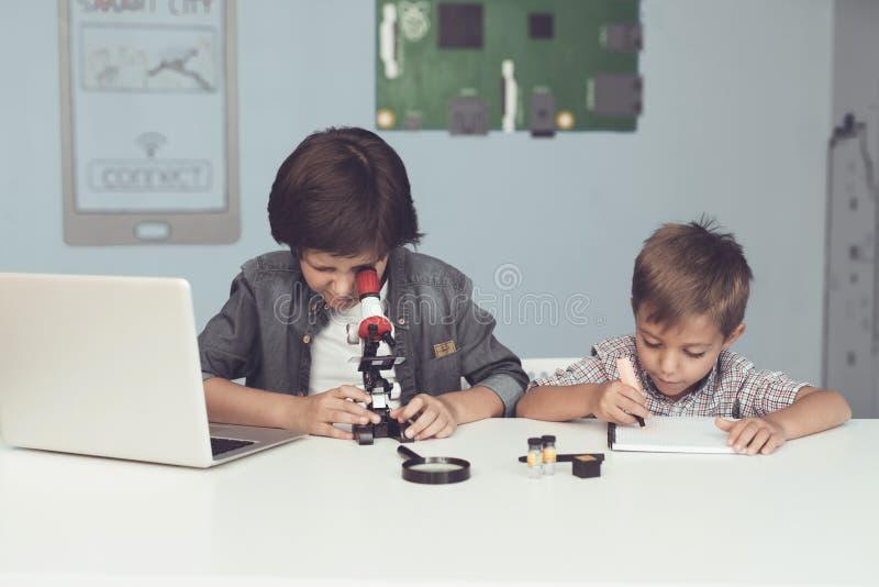 Dois meninos estão sentando-se na tabela Um deles está sentando-se na frente de um portátil cinzento Trabalham na tabela foto de stock