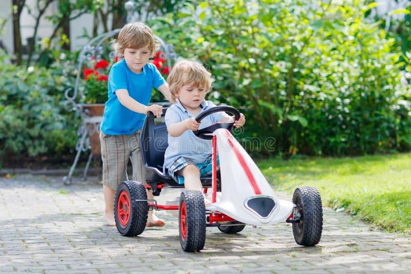 Dois meninos felizes da criança que têm o divertimento com carro do brinquedo foto de stock royalty free
