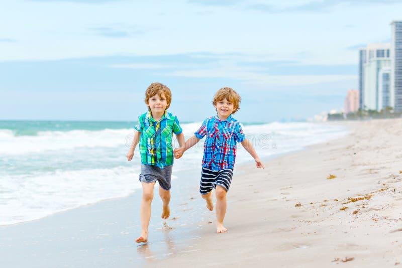 Dois meninos felizes das crianças que correm na praia do oceano Crianças, irmão engraçado e melhores amigos bonitos fazendo féria imagens de stock royalty free