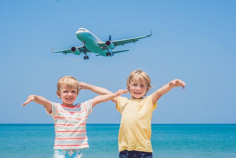 Dois meninos felizes na praia e em um plano de aterrissagem Viagem com conceito das crianças fotografia de stock royalty free