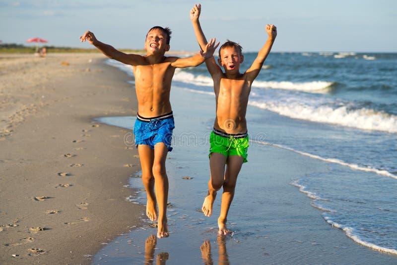 Dois meninos felizes que correm no mar encalham no verão com AR aumentada imagens de stock royalty free