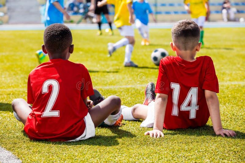 Dois meninos multirraciais novos que vestem a camiseta de futebol vermelha que senta-se na grama no campo de futebol e que apoiam imagens de stock royalty free