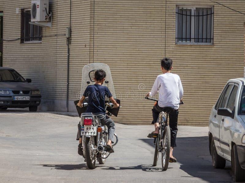 Dois meninos novos, adolescentes, montando um motocycle e uma bicicleta nas ruas do Kashan velho, a cidade principal de Irã centr fotografia de stock