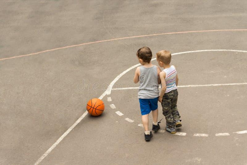Dois meninos novos em um campo de básquete fotos de stock royalty free
