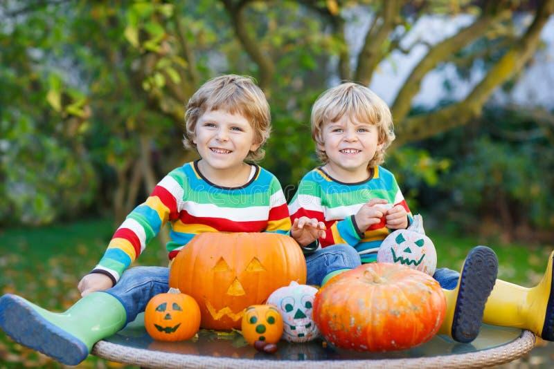 Dois meninos pequenos dos amigos que fazem a jaque-o-lanterna para o Dia das Bruxas na fotografia de stock