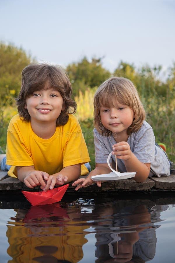 Download Dois Meninos Permitiram Os Barcos De Papel Do Cais Do Rio Imagem de Stock - Imagem de origami, idéias: 107528173