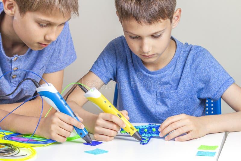 Dois meninos que criam com as penas da impressão 3d imagens de stock royalty free