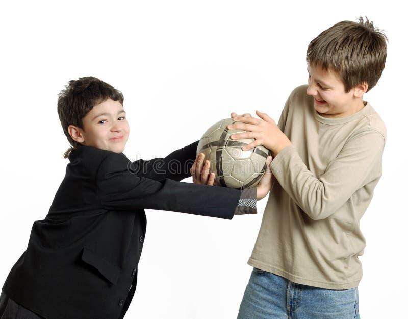 Dois meninos que jogam com o futebol isolado no branco fotografia de stock royalty free