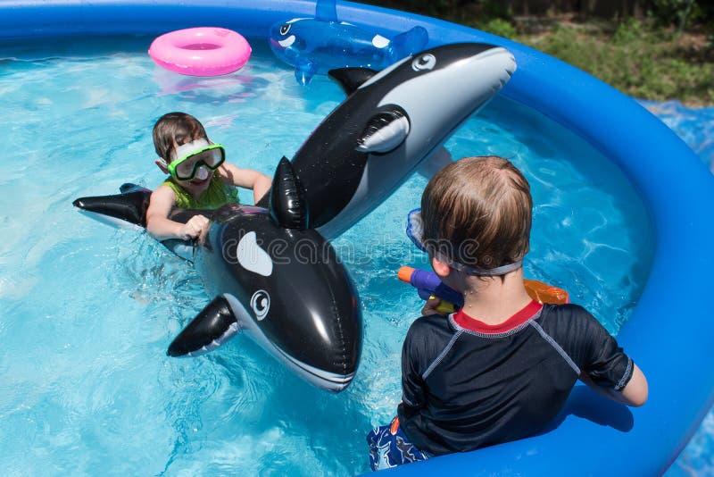 Dois meninos que jogam com os flutuadores na piscina do quintal imagens de stock royalty free