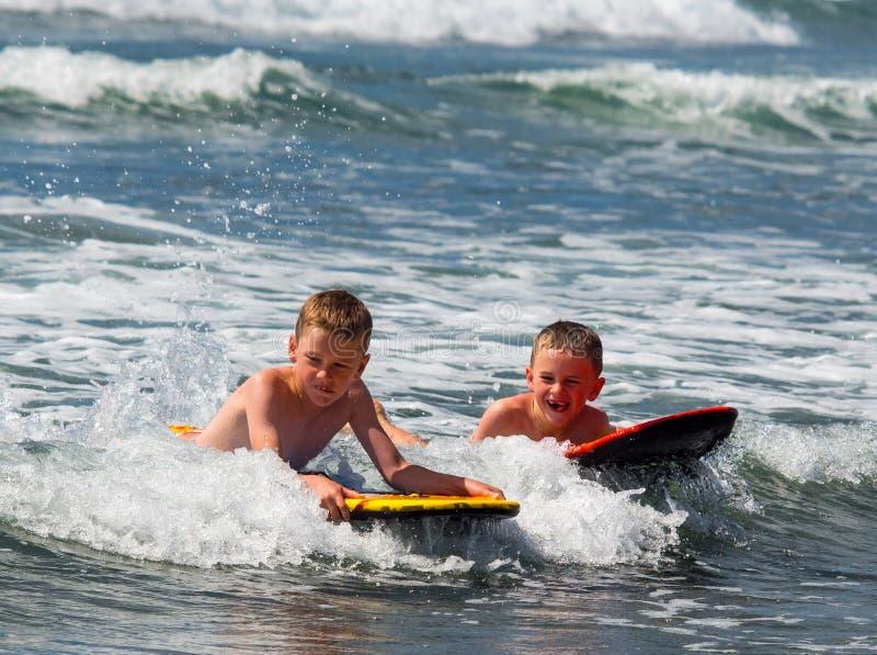 Dois meninos que jogam na ressaca foto de stock royalty free