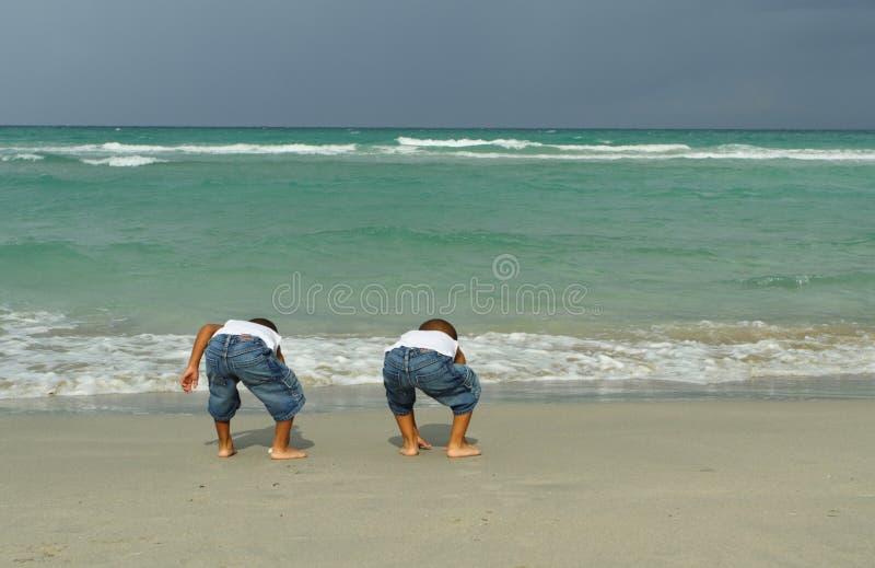 Dois meninos que jogam pela costa imagens de stock