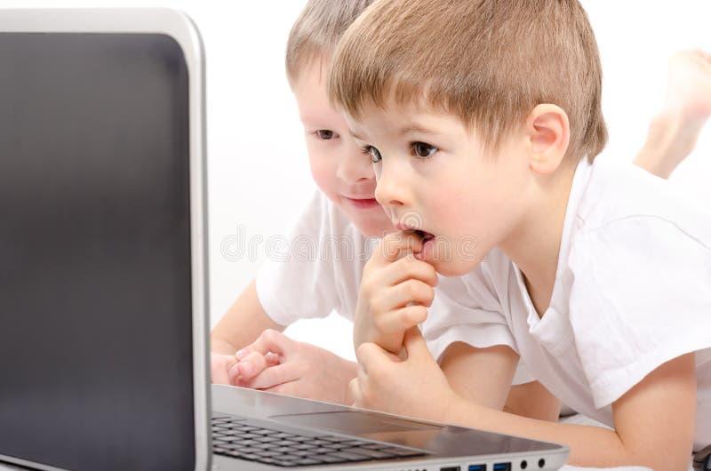 Dois meninos que olham na tela do portátil fotografia de stock royalty free